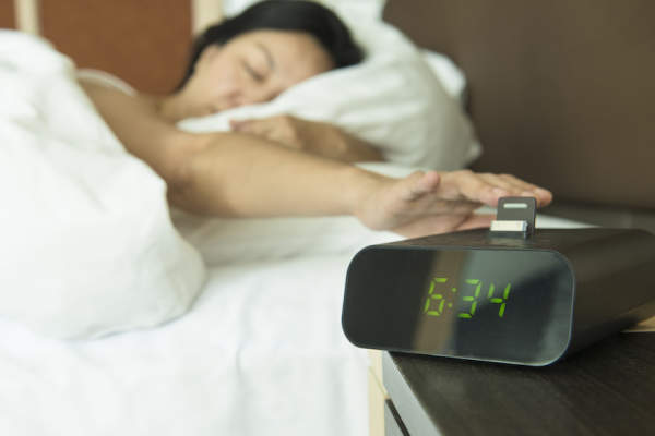 Digital alarm clock turned away from bed.
