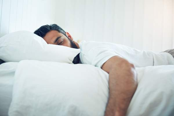 Man sleeping soundly on bed.