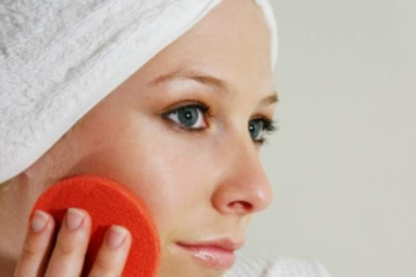 Woman keeping her skin looking good using exfoliating pad.