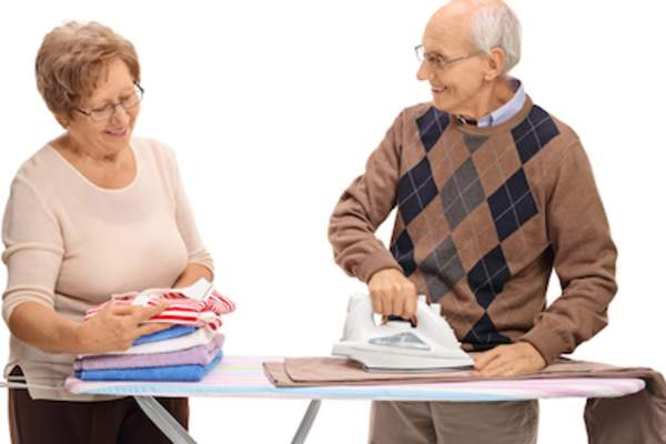 Happy older couple folding and ironing together.
