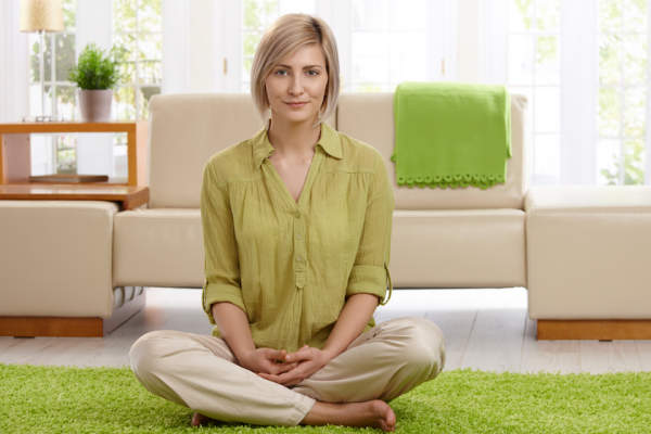 Happy woman sitting on  carpet in her living room.