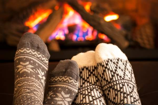 Comfy socks near a fireplace.