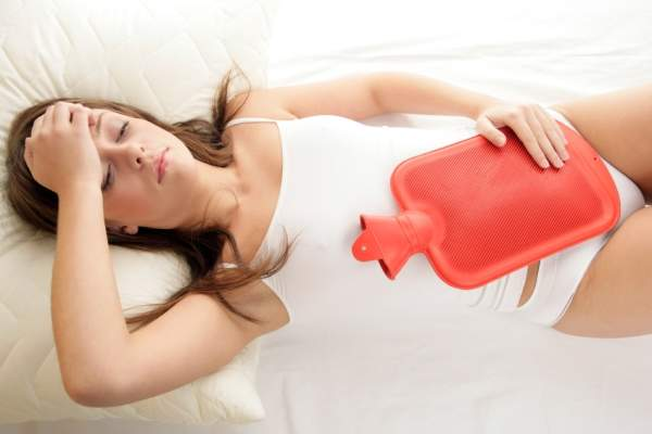A woman holds a hot water bottle to her abdomen to soothe menstrual cramps.