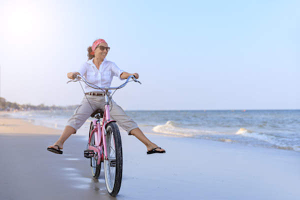 Middle aged woman riding cruiser bike on beach.