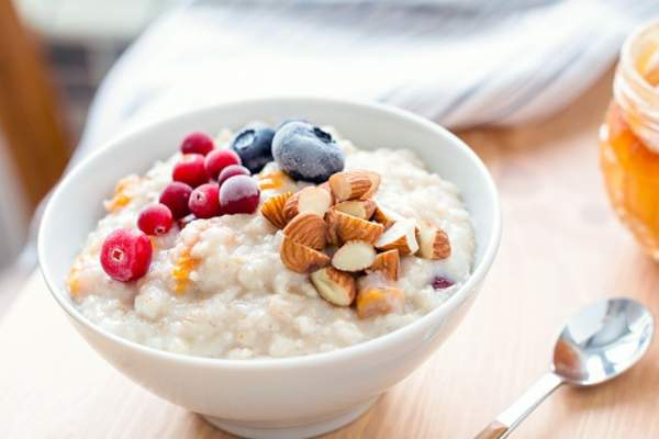 Oatmeal porridge with berries and nuts in bowl.
