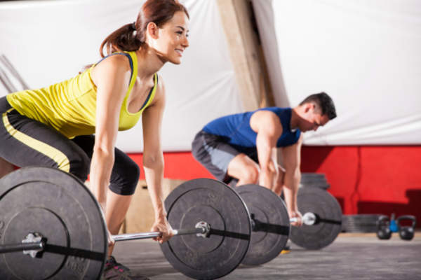 Man and woman lifting at the gym.