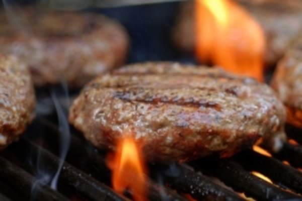 Hamburgers grilling on open flame.