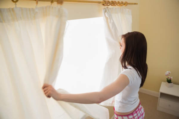 Young woman opening curtains.