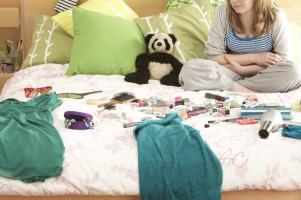 Teen girl in bedroom with items on bed.