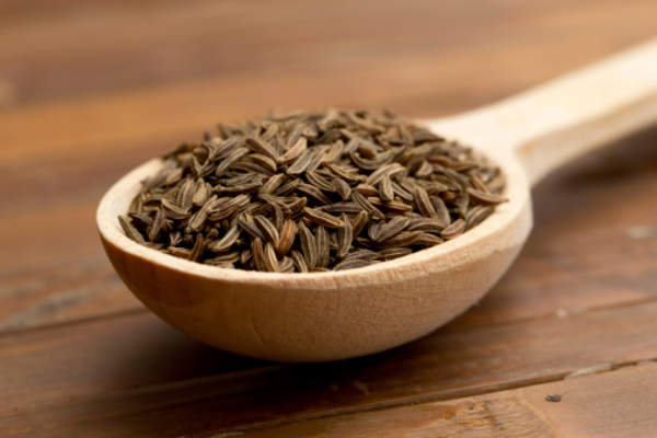 cumin seeds in a wood spoon