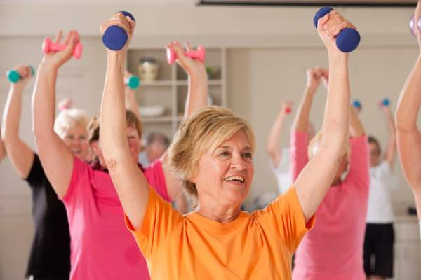 Smiling woman lifte=ing weights in exercise class.
