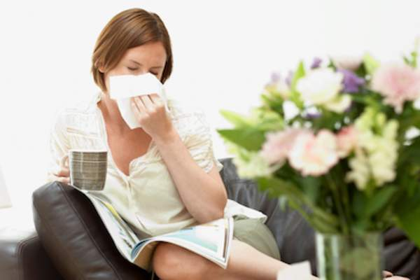 Woman sitting on couch, blowing nose in tissue.