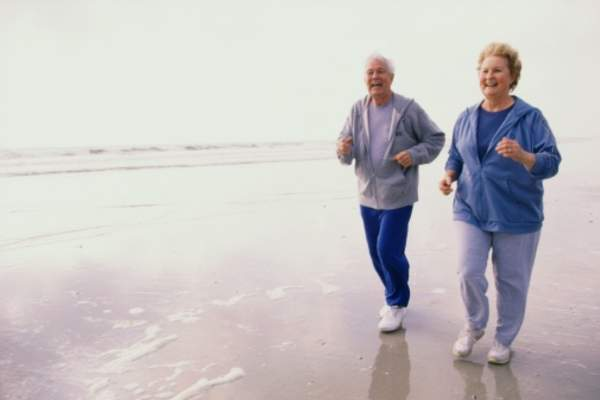 older couple jogging on beach