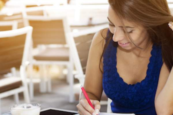 Woman out for coffee writing in journal.