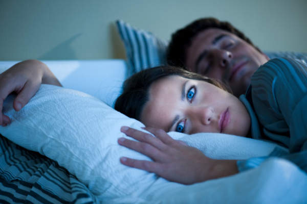 Woman wide awake in bed next to husband.