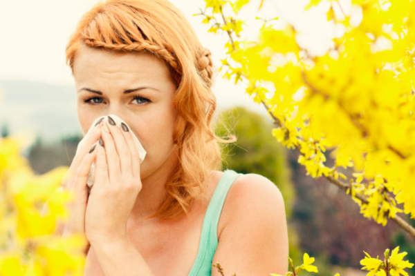Woman blowing her nose while outside on summer day.