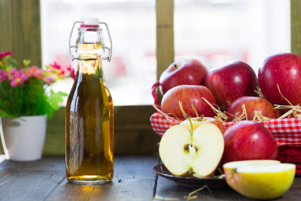 Bottle of apple cider vinegar and fresh apples.