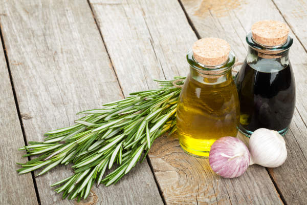 Bottle of vinegar with rosemary and an onion.