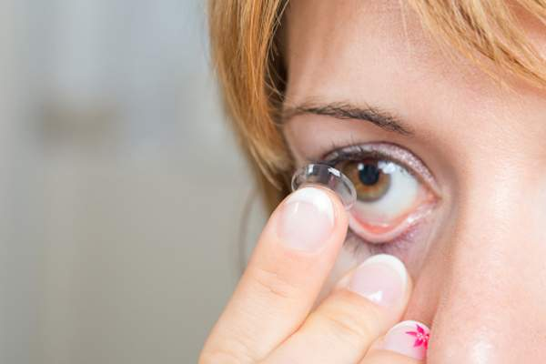 Young woman putting in a contact lens.