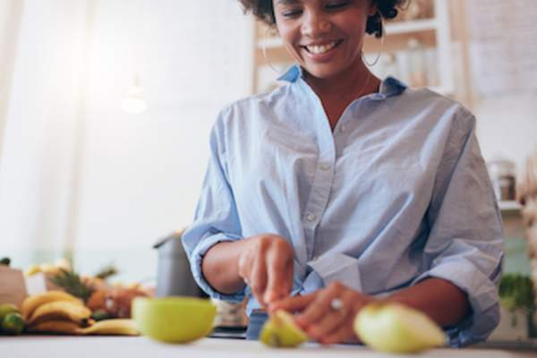 Woman cutting up fruit with rolled up sleeves