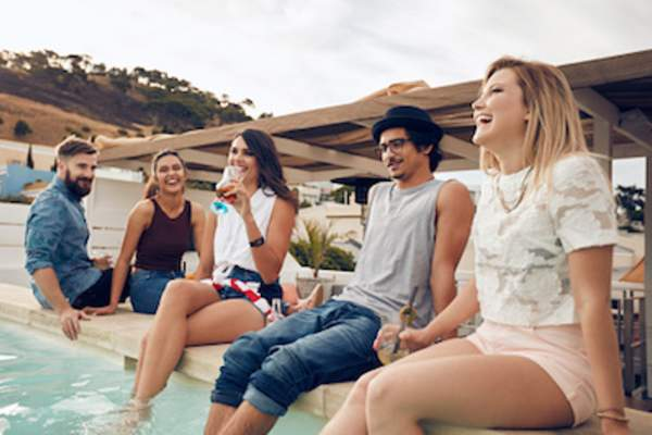 Group sitting around pool during summer