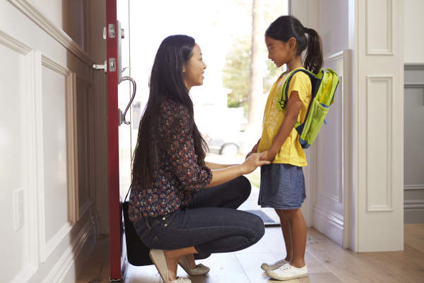 Mother and daughter with backpack in school hallway.