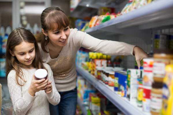 Mother and young daughter at grocery store shopping.