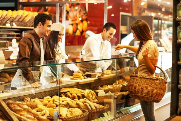 Woman picking up baked goods at bakery.
