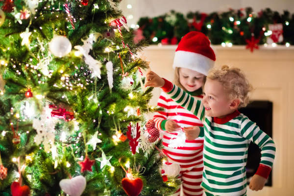 Toddlers hanging ornaments on a Christmas tree.