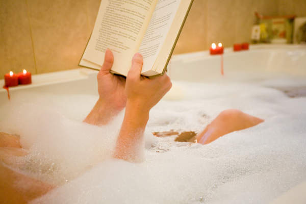 Woman relaxing in bathtub reading a book.