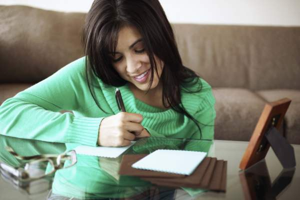 Young smiling woman writing notes.