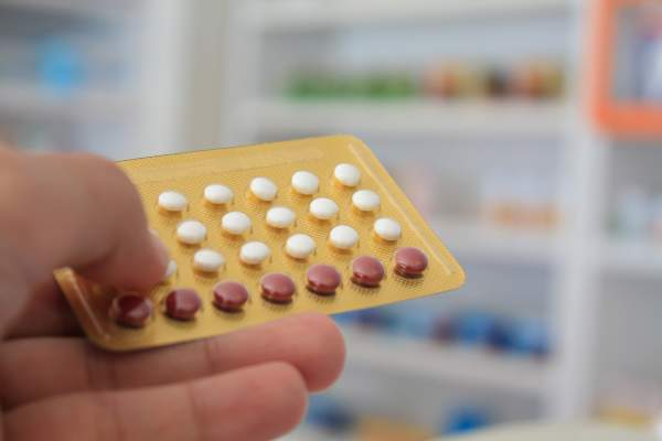 A person holds a birth control pill pack.