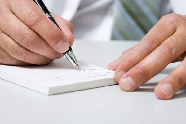 A doctor writes on a prescription pad.
