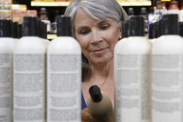 Woman reading ingredients on shampoo bottle.