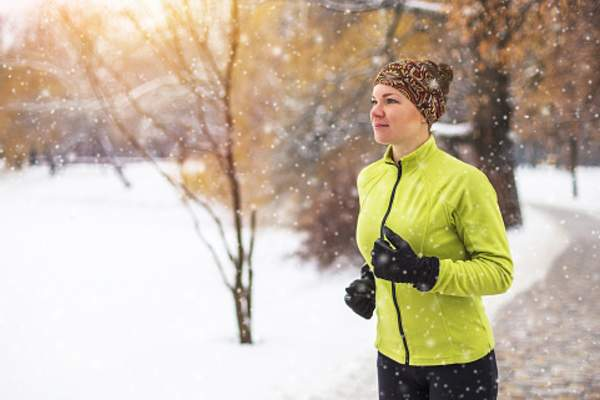 Woman jogging in the snow.