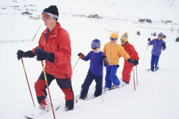 Family walking through the snow in winter gear.
