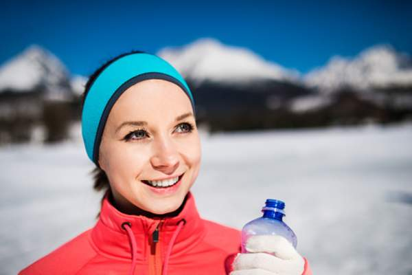 Woman holding water bottle outside in the winter.