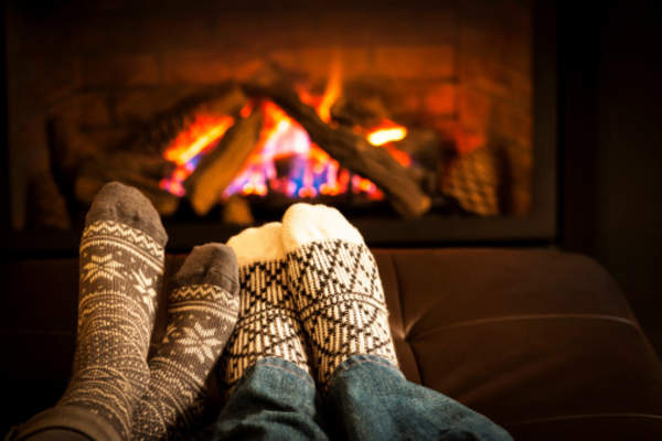 Couple cuddling in front of a fireplace.