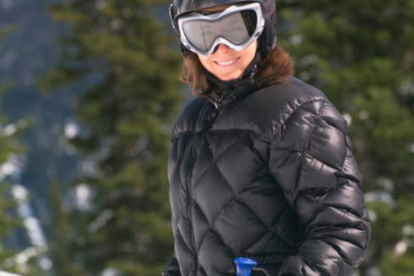 Skiier outside in the winter wearing a winter jacket, helmet, and goggles.