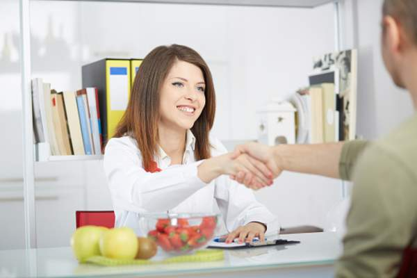 Nutritionist shaking a patient's hand.