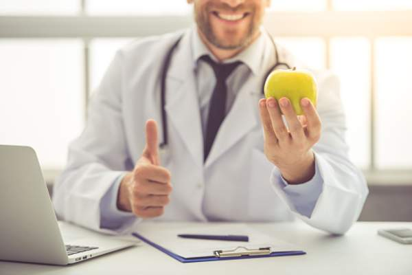 Smiling doctor holding an apple.