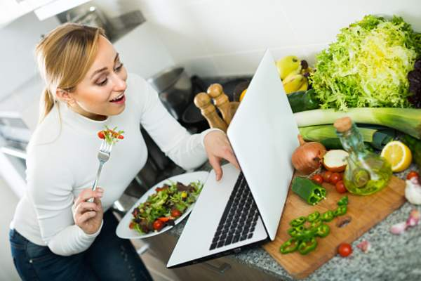 Woman on a laptop eating a salad.