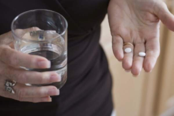 Woman taking pills with water