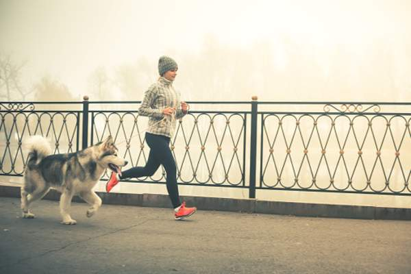 Woman taking an early morning run with her dog.