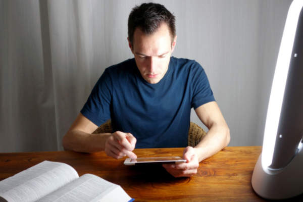 Man working on tablet and reading book late at night.