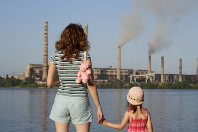 Mother and daughter looking at chemical plant near their home.