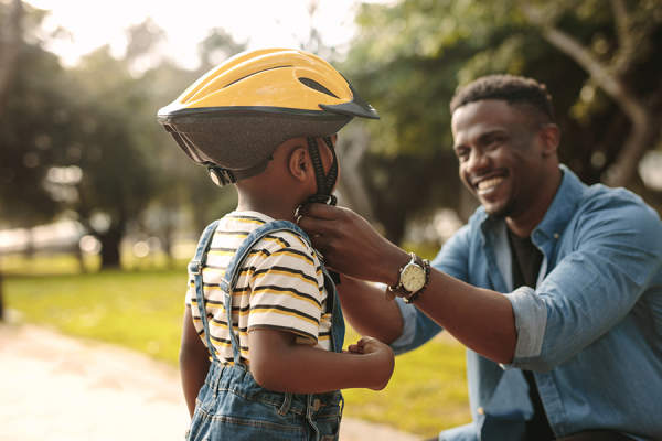 Father adjusting his son's helmet