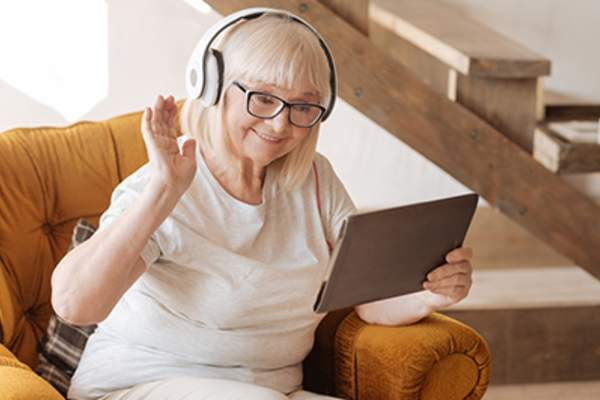 Happy senior woman on tablet wearing headphones.