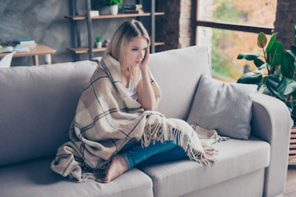 woman on couch, wrapped in throw, in a general malaise.