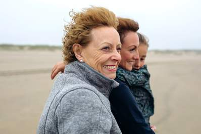 Three generations of smiling women on the beach.